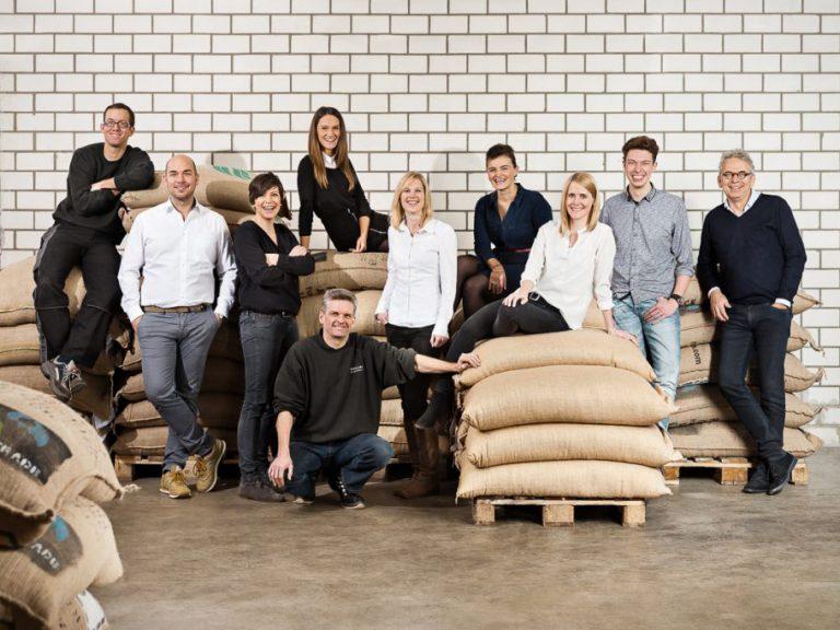 Das Team von der Firma Vollmer Kaffee sitzend und stehend vor Jutesäcken voll mit Kaffeebohnen für ein Businesshooting