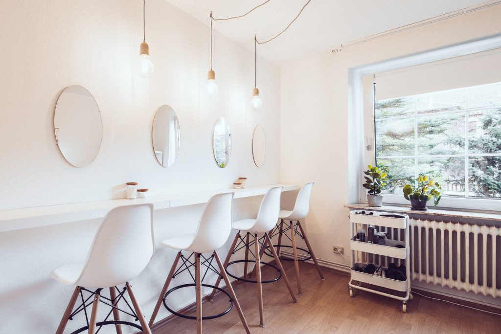 Beautyworkshopraum in dem Make-up und Haarstyling Workshops stattfinden mit vier Spiegeln an den Wänden und vier Barhockern