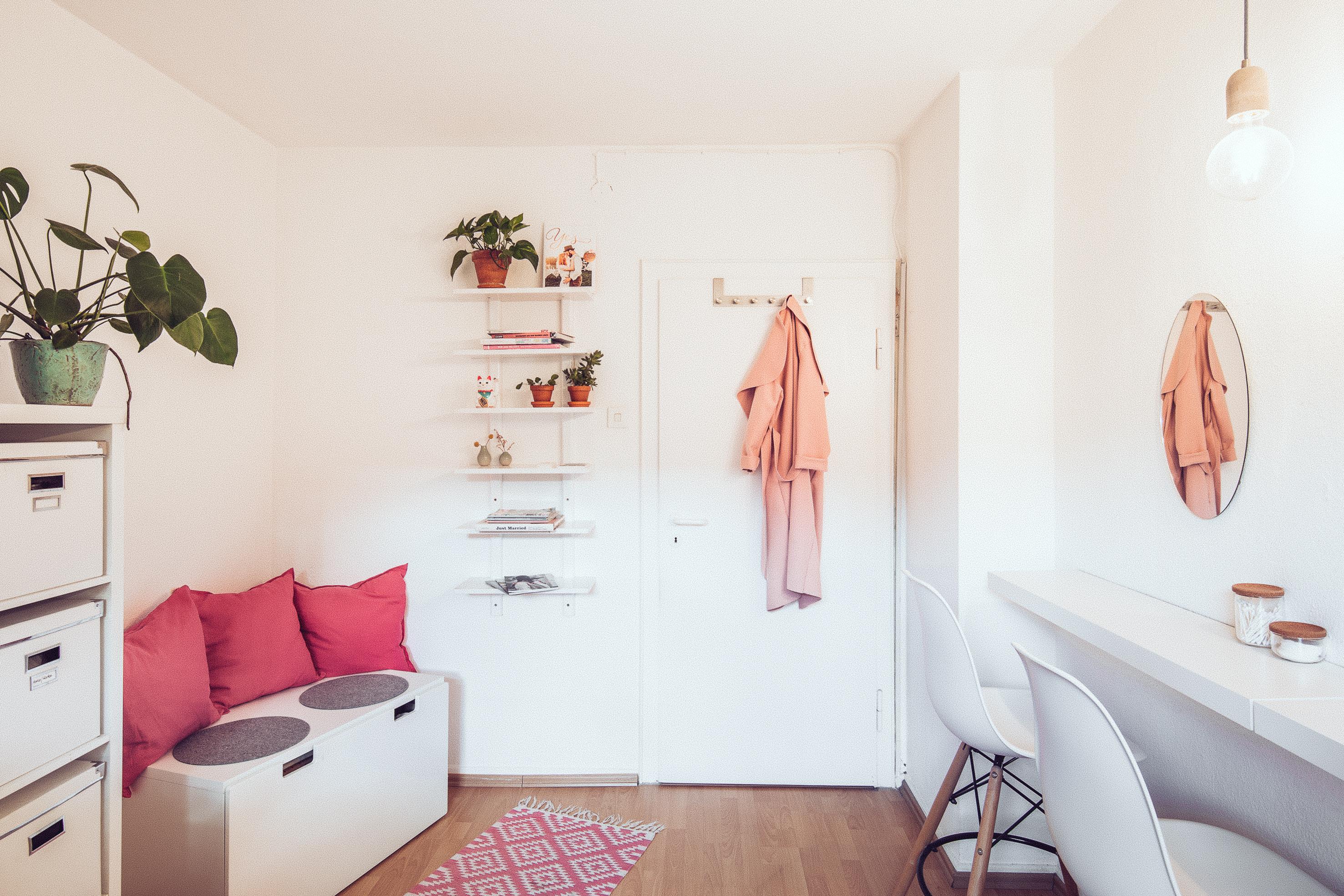 Beauty Workshopraum für Make-up Workshops mit einer Sitzbank und Barhockern alles in weiss gehalten und mit pinken Details wie Kissen
