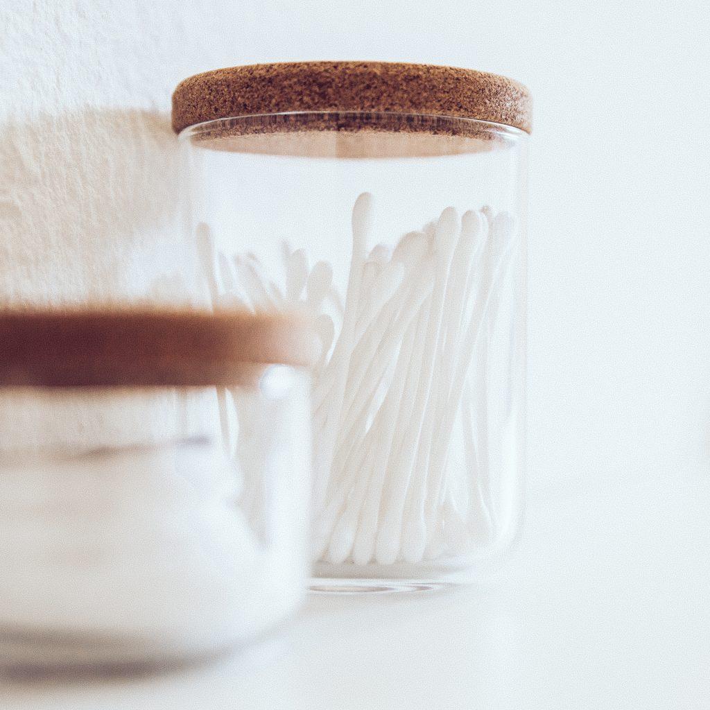 Wattepads und QTipps in einem Behälter zum entfernen von Augen und Lippen Make-up