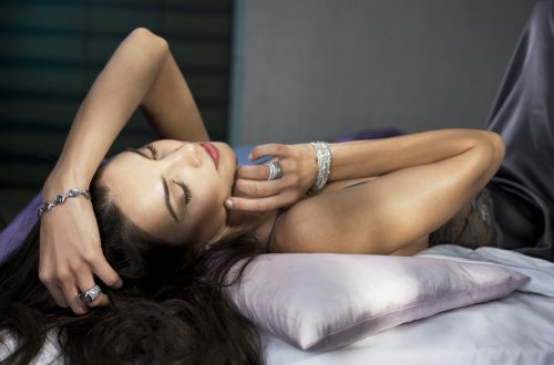 pinffarbender Lippenstift bei dunkelhariger Frau die rücklings auf dem Bett liegt und ein Diamantarmband und einen großen ring trägt
