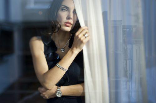 Frau mit lockiger offener Frisur und natürlichem Lippenstift steht am Fenster und lehnt sich an