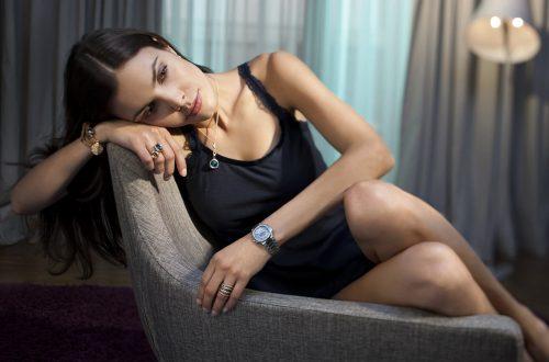 Smokey Eyes bei dunkelhariger Frau die im Neglige auf einem Sessel in einem Hotelzimmer sie trägt eine Kette und Ringe von Oeding-Erdel