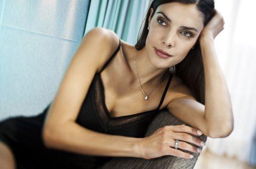 Dunkelharige Frau mit Smokey Eyes und nudefarbenden Lippenstift sitzt im Neglige auf einem Sessel im Hotelzimmer im Factory Hotel.