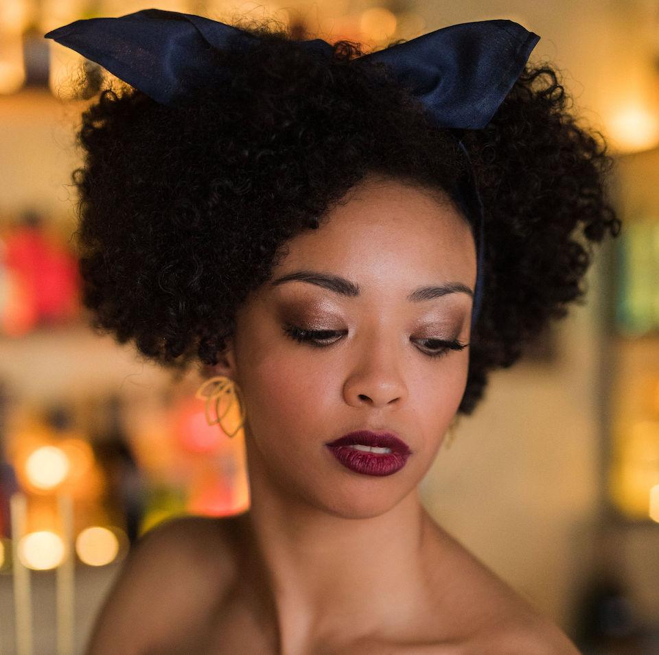 Augen Makeup Smokey Eyes bei dunkelhäutiger Frau mit dunkelrotem Lippenstift mit Afro und Bandana in den Haaren in der Bar Levin in Münster